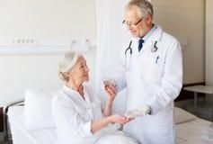 Arts die geneeskunde geven aan hogere vrouw bij het ziekenhuis Royalty-vrije Stock Fotografie