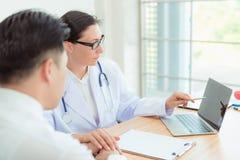 Arts die haar mannelijke patiënt geruststellen en gezondheidsprobleem raadplegen stock fotografie