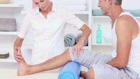 Arts die haar patiëntenknie masseren stock footage