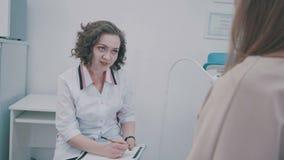 Arts die haar vrouwelijke patiënt raadplegen Geduldige zitting op artsenkantoor stock videobeelden