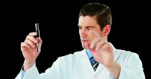 Arts die het digitale scherm met behulp van terwijl het onderzoeken van chemisch product in reageerbuis stock videobeelden