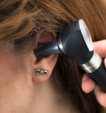 Arts die het oor van de patiënt met oorspiegel controleren stock afbeelding