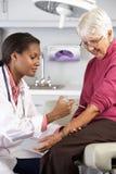 Arts die Hogere Vrouwelijke Geduldige Injectie geven Stock Afbeelding