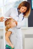 Arts die hoogte van een meisje meten stock foto