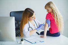 Arts die inenting in wapen inspuiten weinig kindmeisje, gezonde stock afbeelding