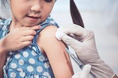 Arts die inenting in wapen van Aziaat inspuiten weinig kindmeisje royalty-vrije stock afbeeldingen