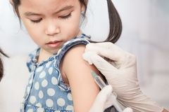 Arts die inenting in wapen van Aziaat inspuiten weinig kindmeisje stock foto