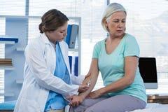 Arts die injectie geven aan patiënt Stock Fotografie