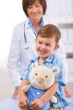 Arts die kind onderzoekt Stock Afbeeldingen