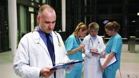 Arts die klembord in het ziekenhuisgang bekijken stock video