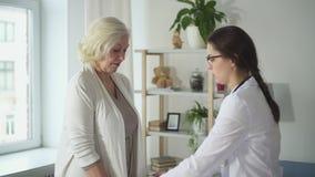 Arts die lichte oefeningen tonen aan gepensioneerdedame bij haar huis stock videobeelden