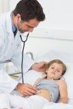 Arts die maag van ziek meisje onderzoeken Stock Foto