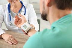 Arts die man impuls met medisch apparaat in het ziekenhuis controleren stock fotografie