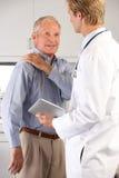 Arts die Mannelijke Patiënt met de Pijn van de Schouder onderzoekt Stock Foto's