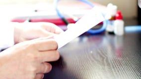 Arts die medische documenten voor medisch onderzoek lezen stock video