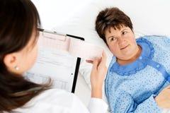 Arts die medische resultaten verklaren aan hogere vrouw stock afbeelding