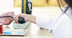 Arts die Mercury-sphygmomanometer met behulp van aan het controleren van de bloeddruk van de patiënt in het ziekenhuis stock videobeelden