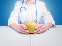 Arts die met appelen bij de lijst zitten Stock Foto