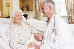 Arts die met Hogere Vrouw in het Ziekenhuis lacht royalty-vrije stock afbeeldingen