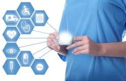 Arts die modern medisch apparaat en informatiepictogrammen op witte achtergrond gebruiken stock afbeeldingen