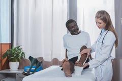 Arts die op gipsverband op verwond Afrikaans Amerikaans geduldig been zetten stock afbeeldingen