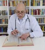 Arts die op informatie over geneeskunde kijkt Stock Afbeeldingen