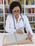 Arts die op informatie over geneeskunde kijkt Stock Afbeelding