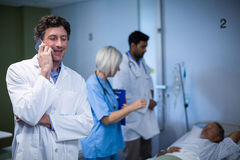 Arts die op mobiele telefoon in het ziekenhuis spreken Royalty-vrije Stock Afbeelding