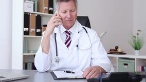 Arts die op zijn mobiele telefoon babbelen stock footage