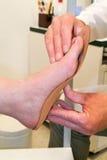 Arts die orthopedische binnenzolen voor een patiënt voorbereiden stock foto