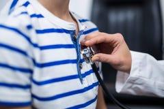 Arts die patiënt met een stethoscoop onderzoeken Stock Afbeelding