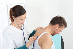 Arts die patiënt met stethoscoop onderzoekt Royalty-vrije Stock Foto