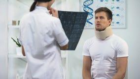 Arts die patiënt in schuim cervicale kraag informeren over goed x-ray resultaat, rehab stock videobeelden
