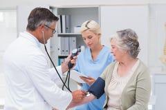 Arts die patiëntenbloeddruk controleren terwijl verpleegster die van het nota nemen Royalty-vrije Stock Foto's