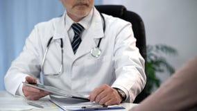 Arts die patiëntengegevens over tablet controleren, die medische dossiers, overleg houden royalty-vrije stock fotografie