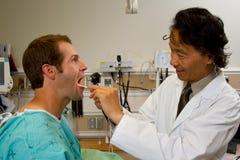 Arts die patiëntenkeel bekijken Stock Foto