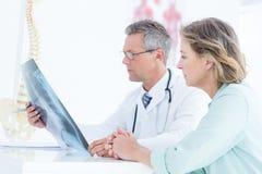 Arts die röntgenstraal tonen aan zijn patiënt stock foto