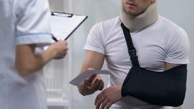 Arts die rekening geven aan de mens in schuimkraag en wapenslinger, dure behandeling stock videobeelden