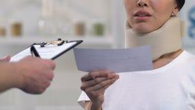Arts die rekening geven aan vrouw in schuim cervicale kraag, dure behandeling stock videobeelden