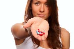 Arts die rood en blauwe pillencapsules aanbiedt Stock Foto