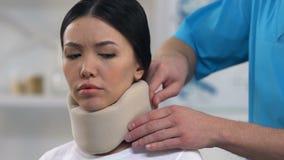 Arts die schuim cervicale kraag toepassen op vrouwelijke, ongemakkelijke medische steun stock video