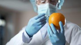 Arts die serum inspuiten in sinaasappel, die procedure van liposuction tonen aan cliënten stock fotografie