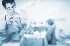 Arts die spuit op vage achtergrond met teamchirurg in werkende ruimte, concept voor gezondheidszorg en geneeskunde gebruiken Royalty-vrije Stock Afbeelding