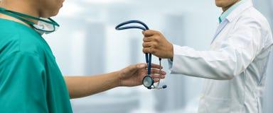 Arts die stethoscoop geven aan chirurg Referral Royalty-vrije Stock Foto's