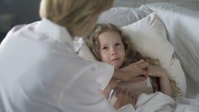 Arts die stethoscoop met behulp van om ziek meisje te onderzoeken, kind die aan koorts lijden stock video