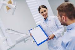 Arts die tandresultaten tonen aan patiënt stock afbeeldingen
