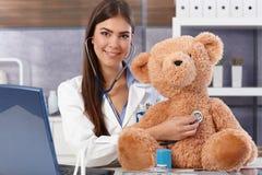 Arts die teddybeer onderzoekt Stock Afbeelding