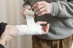 Arts die Verband op Verwonde Hand toepast Stock Foto