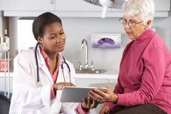 Arts die Verslagen bespreken met Hogere Vrouwelijke Patiënt Stock Fotografie