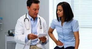 Arts die voorschrift geven aan vrouwelijke patiënt stock video